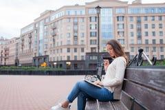 Ein schönes junges Mädchen mit dem langen braunen Haar, das auf der Bank mit Buch und beißenden Gläsern beim Ablesen sitzt Sie ve Lizenzfreies Stockfoto