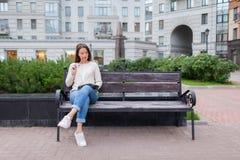 Ein schönes junges Mädchen mit dem langen braunen Haar, das auf der Bank mit Buch und beißenden Gläsern beim Ablesen sitzt Sie ve Lizenzfreie Stockbilder