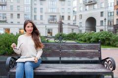Ein schönes junges Mädchen mit dem langen braunen Haar, das auf der Bank mit dem Buch und den Brillen in seinen Händen sitzt Sie  Lizenzfreies Stockbild