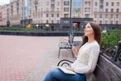 Ein schönes junges Mädchen mit dem langen braunen Haar, das auf der Bank mit dem Buch und den Brillen in seinen Händen sitzt Sie  Lizenzfreie Stockbilder