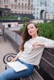 Ein schönes junges Mädchen mit dem langen braunen Haar, das auf der Bank mit dem Buch und den Brillen in seinen Händen sitzt Sie  Lizenzfreie Stockfotografie