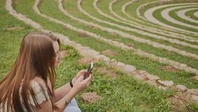 Ein schönes junges Mädchen mit einem Handy in ihren Händen sitzt auf dem Gras unter einem großen grünen Stadion erholung stock video