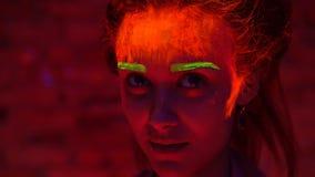 Ein schönes junges Mädchen mit glühender Farbe auf ihrem Gesicht und Haar in der schwarzen Lichtunterhaltung Hübsche Frau mit dem stock video