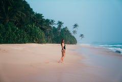 Ein schönes junges Mädchen schlendert entlang einen tropischen Strand mit rosa Sand, trägt einen stilvollen Badeanzug, bewundert  stockfotos