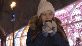 Ein schönes junges Mädchen wartet auf ihren Freund auf einem Datum Sie war sehr kalt, also trinkt sie heißen Tee stock footage
