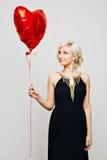 Ein schönes junges sexy blondes Mädchen mit dem gelockten blonden Haar in einem langen eleganten schwarzen Kleid mit vergoldetem  Lizenzfreies Stockbild