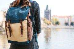 Ein schönes junges touristisches Mädchen mit einem Rucksack steht nahe bei dem die Moldau-Fluss in Prag und bewundert eins von de stockfotos