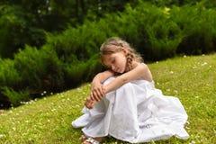 Ein schönes kleines Mädchen, das auf dem hellgrünen Gras sitzt und ihre Knie mit ihr umfasst Lizenzfreies Stockfoto