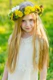 Ein schönes kleines Mädchen läuft durch einen blühenden Garten im s Lizenzfreies Stockbild