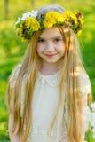 Ein schönes kleines Mädchen läuft durch einen blühenden Garten im s Lizenzfreies Stockfoto