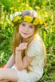 Ein schönes kleines Mädchen läuft durch einen blühenden Garten im s Stockbild