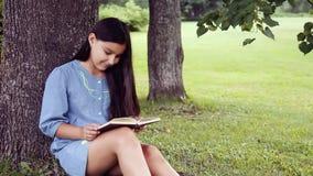 Ein schönes kleines Mädchen mit dem langen Haar liest ein Buch, das unter einem Baum und Träumen über angenehmes etwas sitzt stock video