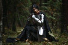 Ein schönes Kriegersmädchen mit einem Klinge tragenden chainmail und Rüstung in einem mysteriösen Wald Lizenzfreies Stockfoto