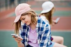 Ein schönes lächelndes blondes Mädchen, das kariertes Hemd und eine Kappe trägt, sitzt auf dem Sportfeld mit einem Telefon in ihr lizenzfreies stockfoto
