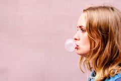 Ein schönes Mädchen auf einem Hintergrund einer rosa Tönung steht im Profil und stößt ein Ball des Kaugummis luft stockbild