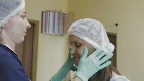 Ein schönes Mädchen bereitet sich für ein Verfahren in einem Cosmetologyraum vor stock video