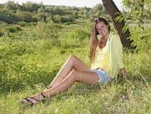 Ein schönes Mädchen, das auf Gras sitzt Lizenzfreie Stockbilder
