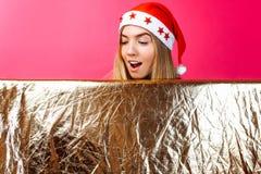 Ein schönes Mädchen, das einen Sankt-Hut und mit Lametta auf ihrem Hals, das Mädchen trägt, hält eine leere goldene farbige Ansch stockfotos