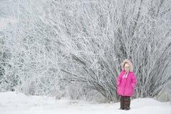 Ein schönes Mädchen, das am erstaunlichen Winterbaum steht Stockfoto
