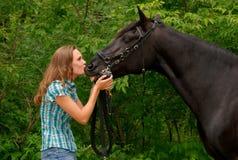 Ein schönes Mädchen, das ihr stattliches Pferd küßt Stockfotografie