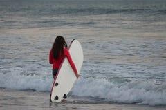 Ein schönes Mädchen, das mit Surfbrett in einem Meer steht lizenzfreies stockfoto