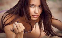 Ein schönes Mädchen in einem Bikini gießt Sand Stockfotografie
