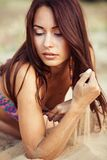Ein schönes Mädchen in einem Bikini gießt Sand stockfoto