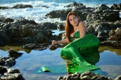 Ein schönes Mädchen in einem grünen Meerjungfraukostüm liegt im Wasser unter den Steinen auf dem Strand und betrachtet die Kamera lizenzfreie stockfotografie