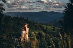 Ein schönes Mädchen in einem Kleid und ein Blumenstrauß von Blumen in ihrer Hand Stockfotos