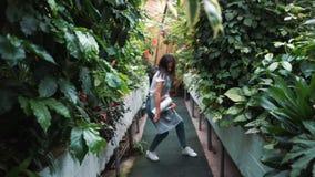 Ein schönes Mädchen in einem Schutzblechtanzen in einem Gewächshaus Florist glücklich, Tanzen und Lachen stock video footage