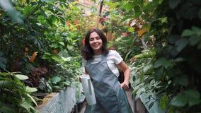 Ein schönes Mädchen in einem Schutzblechtanzen in einem Gewächshaus Florist glücklich, Tanzen und Lachen stock footage
