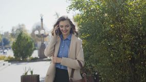 Ein schönes Mädchen in einem weißen Mantel spricht telefonisch stock footage