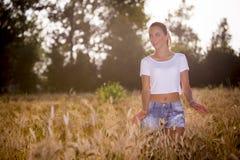 Ein schönes Mädchen in einem Wheatfield auf Sonnenuntergang Lizenzfreies Stockbild