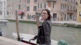 Ein schönes Mädchen in einer Lederjacke geht auf italienisch Venedig Frauentourist ist über ihre Ferien in Europa glücklich stock footage