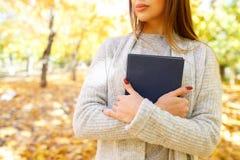 Ein schönes Mädchen in einer weißen Strickjacke hält ein Buch auf dem Hintergrund des Herbstparks Stockfoto