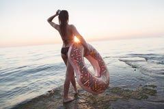 Ein schönes Mädchen geht das Meer mit einem großen Kreis stockfotografie