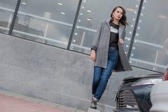 Ein sch?nes M?dchen geht durch die Stadt hinter einem Parkplatz nahe bei einem Einkaufszentrum Brunette in einem Mantel und in de stockfoto