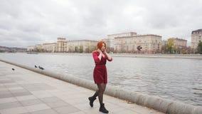 Ein schönes Mädchen geht entlang die Promenade und die Tänze stock footage