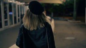 Ein schönes Mädchen im stilvollen Hut und in einer schwarzen Lederjacke geht durch den Nachtpark angesichts der Lampen eines Café stock video footage