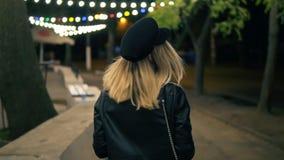 Ein schönes Mädchen im stilvollen Hut und in einer schwarzen Lederjacke geht durch den Nachtpark angesichts der Lampen eines Café stock video