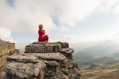 Ein schönes Mädchen meditiert in einer Lotoshaltung, die auf einem Felsen über den Wolken gegen den Hintergrund des Sonnenunterga Stockfoto