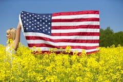 Ein schönes Mädchen mit amerikanischer Flagge auf dem gelben Gebiet Stockfotos