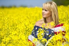 Ein schönes Mädchen mit amerikanischer Flagge auf dem gelben Gebiet Stockbilder