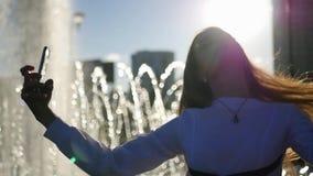 Ein schönes Mädchen mit dem langen Haar wirft auf der Kamera, macht ein Foto auf, das am Brunnen mit den unscharfen Strahlen von  stock footage