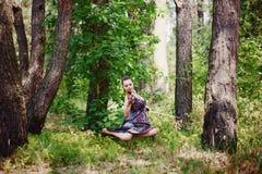Ein schönes Mädchen mit einer Violine in einem langen Kleid schwebt unter den Bäumen Lizenzfreie Stockfotos