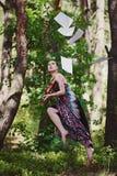 Ein schönes Mädchen mit einer Violine in einem langen Kleid schwebt unter den Bäumen Stockbilder