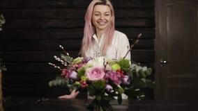 Ein schönes Mädchen mit rosa Haarlächeln, bewundert einen erstaunlichen Blumenstrauß von den Blumen, die auf dem Oberflächen gege stock footage