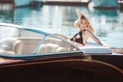 Ein schönes Mädchen, ein Modell in einem Badeanzug und ein breitrandiger Hut lizenzfreies stockbild