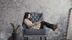 Ein schönes Mädchen sitzt auf einem weichen Lehnsessel in einem Kunststudio und betrachtet die Arbeiten, die vom Maskenbildner Fa stock video