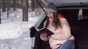 Ein sch?nes M?dchen sitzt in einem Auto in einem Winterwald und in den leichten Schl?gen durch das Tagebuch stock footage